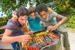 Adolescentes durante una barbacoa en el Bbq del jardín de la familia Fotos de archivo