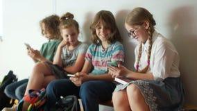 Adolescentes e smartphones As crianças usam smartphones durante a ruptura da escola Um grupo de alunos que sentam-se em um banco vídeos de arquivo