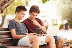 Adolescentes en banco de parque usando el ordenador portátil y la tableta de Digitaces Fotografía de archivo