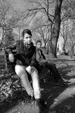 Adolescentes en banco en parque Foto de archivo libre de regalías