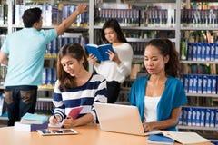 Adolescentes en biblioteca Foto de archivo