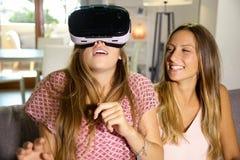 Adolescentes en casa que miran la simulación de la realidad virtual Fotos de archivo