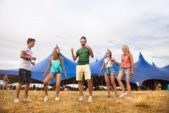 Adolescentes en el baile del festival de música del verano delante de la tienda Foto de archivo libre de regalías