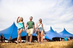 Adolescentes en el festival de música del verano delante de la tienda azul grande Fotografía de archivo libre de regalías