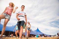 Adolescentes en el festival de música del verano delante de la tienda azul grande Foto de archivo libre de regalías