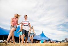 Adolescentes en el festival de música del verano delante de la tienda azul grande Imagen de archivo libre de regalías