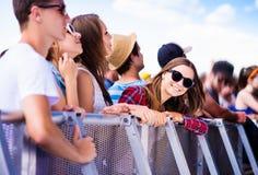 Adolescentes en el festival de música del verano, en la barrera Imagen de archivo libre de regalías