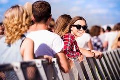 Adolescentes en el festival de música del verano, en la barrera Foto de archivo