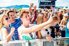 Adolescentes en el festival de música del verano en la muchedumbre que toma el selfie Fotos de archivo libres de regalías
