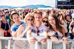 Adolescentes en el festival de música del verano en la muchedumbre que toma el selfie Imagen de archivo