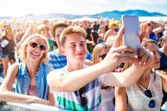 Adolescentes en el festival de música del verano en la muchedumbre que toma el selfie Imágenes de archivo libres de regalías