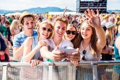 Adolescentes en el festival de música del verano en la muchedumbre que toma el selfie Imagen de archivo libre de regalías