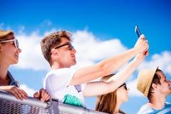 Adolescentes en el festival de música del verano en la muchedumbre que toma el selfie Fotos de archivo