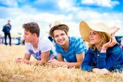 Adolescentes en el festival de música del verano, mintiendo en la tierra Foto de archivo