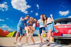 Adolescentes en el festival de música del verano por campervan rojo del vintage Fotografía de archivo