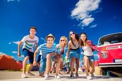 Adolescentes en el festival de música del verano por campervan rojo del vintage Foto de archivo libre de regalías