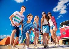 Adolescentes en el festival de música del verano por campervan rojo del vintage Imagen de archivo