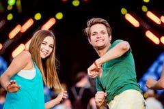 Adolescentes en el festival de música del verano que se divierte, bailando Fotos de archivo libres de regalías