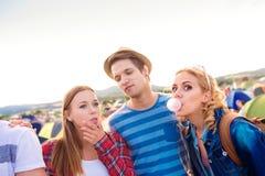 Adolescentes en el festival de música del verano que sopla gomas buble Fotografía de archivo