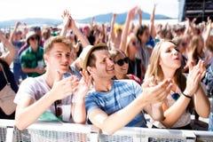 Adolescentes en el festival de música del verano que tiene buen tiempo Foto de archivo libre de regalías