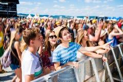 Adolescentes en el festival de música del verano que tiene buen tiempo Imagen de archivo libre de regalías