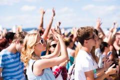 Adolescentes en el festival de música del verano que tiene buen tiempo Fotografía de archivo libre de regalías
