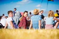 Adolescentes en el festival de música del verano, sentándose en la hierba Imagenes de archivo