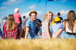 Adolescentes en el festival de música del verano, sentándose en la hierba Fotografía de archivo