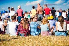 Adolescentes en el festival de música del verano, sentándose en la hierba Imágenes de archivo libres de regalías