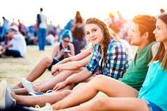 Adolescentes en el festival de música del verano, sentándose en la tierra Imágenes de archivo libres de regalías