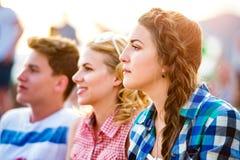 Adolescentes en el festival de música del verano, sentándose en la tierra Imagen de archivo