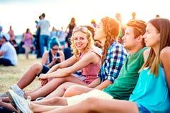 Adolescentes en el festival de música del verano, sentándose en la tierra Fotos de archivo