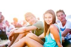 Adolescentes en el festival de música del verano, sentándose en la tierra Imagen de archivo libre de regalías