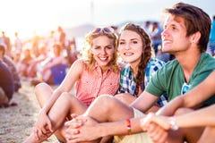 Adolescentes en el festival de música del verano, sentándose en la tierra Fotos de archivo libres de regalías