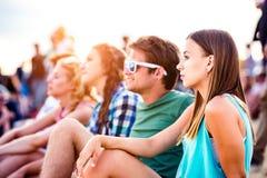 Adolescentes en el festival de música del verano, sentándose en la tierra Imagenes de archivo