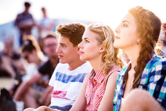 Adolescentes en el festival de música del verano, sentándose en la tierra Foto de archivo libre de regalías