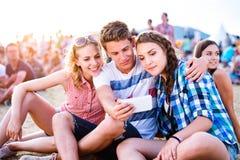 Adolescentes en el festival de música del verano, tomando el selfie con el smartphon Foto de archivo libre de regalías