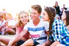 Adolescentes en el festival de música del verano, tomando el selfie con el smartphon Imagen de archivo