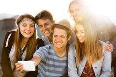 Adolescentes en el festival de música del verano, tomando el selfie con el smartphon Foto de archivo