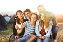 Adolescentes en el festival de música del verano, tomando el selfie con el smartphon Imagen de archivo libre de regalías