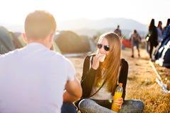 Adolescentes en el festival de música que descansa, comiendo y bebiendo Fotos de archivo libres de regalías