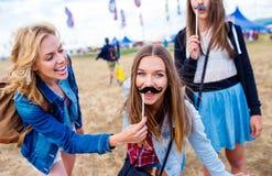Adolescentes en el festival del verano con el bigote falso Imagen de archivo libre de regalías