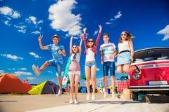 Adolescentes en el festival del verano que salta por campervan rojo del vintage Foto de archivo