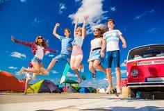Adolescentes en el festival del verano que salta por campervan rojo del vintage Fotografía de archivo libre de regalías