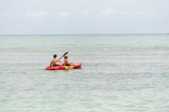 Adolescentes en el mar con una canoa Imagen de archivo libre de regalías