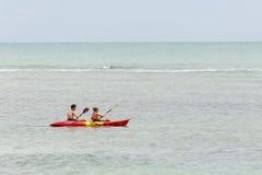 Adolescentes en el mar con una canoa Imagenes de archivo