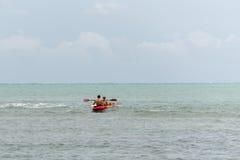 Adolescentes en el mar con una canoa Foto de archivo libre de regalías