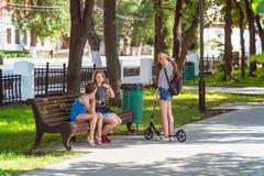 Adolescentes en el parque en el banco Foto de archivo