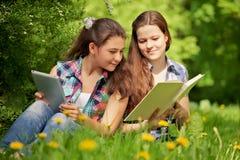 Adolescentes en el parque. bookr u ordenador. Concepto Fotos de archivo libres de regalías