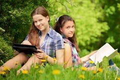 Adolescentes en el parque. bookr u ordenador. Concepto Imagen de archivo